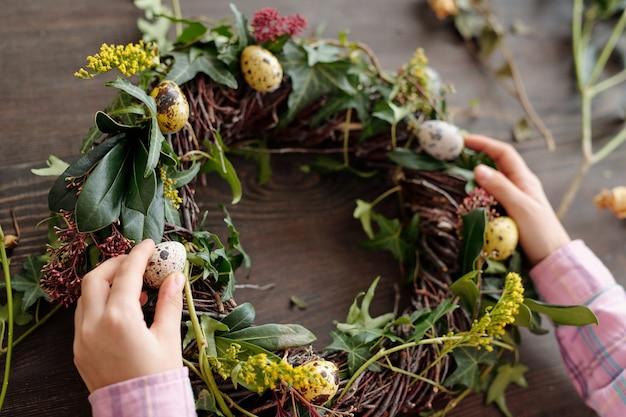 테이블에 메추라기 알로 꽃 화환을 장식하는 어린 소녀의 클로즈업