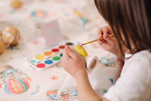 小さな女の子のクローズアップはイースターエッグを手に持って写真を作る