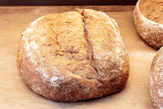 Крупный план буханки черного домашнего хлеба, черного черного хлеба с зернами на полке магазина