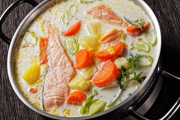 로히케이토의 클로즈업, 크림, 감자, 당근, 리크, 딜을 짙은 나무 테이블에 있는 냄비에 넣은 연어 생선 수프, 핀란드 요리, 고전 요리, 위에서 수평 전망