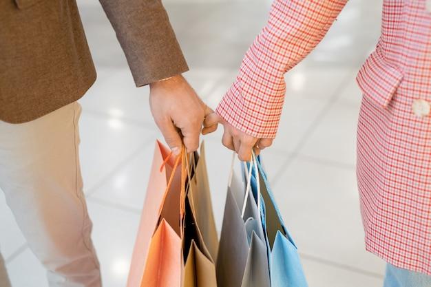 ショッピング中に買い物袋を持っている素敵なカップルのクローズアップ