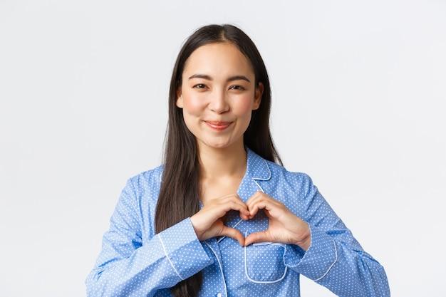 青いパジャマで素敵なフェミニンなアジアの女の子のクローズアップは、愛とケアを表現し、ハートのジェスチャーを示し、何かのように幸せに笑って、白い背景に立って喜んでいます