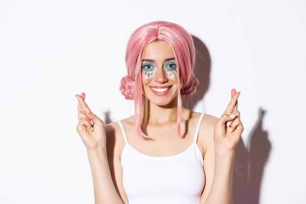 Крупный план прекрасной улыбающейся женщины в хеллоуинском костюме, розовом парике и ярком макияже, с надеждой смотрящей в камеру и загадывающей желание со скрещенными пальцами.