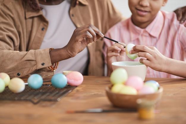 Крупным планом любящие афро-американские мать и дочь вместе рисуют пасхальные яйца, сидя за деревянным столом в уютном домашнем интерьере
