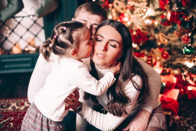 木のそばに座っている優しさで彼女の母親にキスする愛情のある少女のクローズアップ