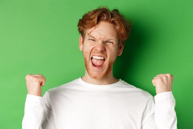 Крупный план счастливого победителя молодого человека, празднующего победу, крича «да» от радости и нагнетающего кулаки, торжествуя на зеленом фоне.