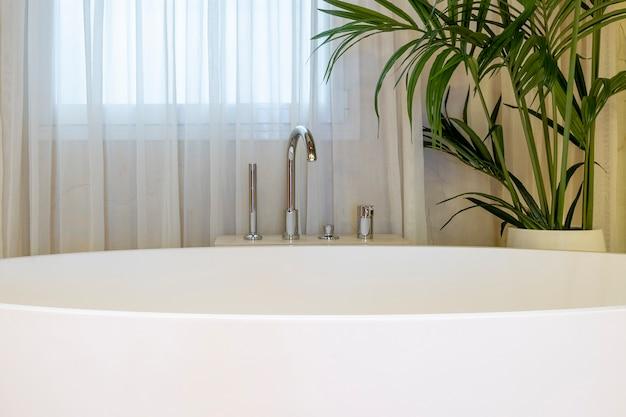 Крупный план роскошного современного дизайна интерьера ванной комнаты с белой ванной и комнатным растением