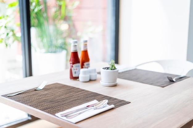 Крупный план роскошной ложки и вилки, вазона для цветов, бутылки соуса, украшение обеденного стола в отеле