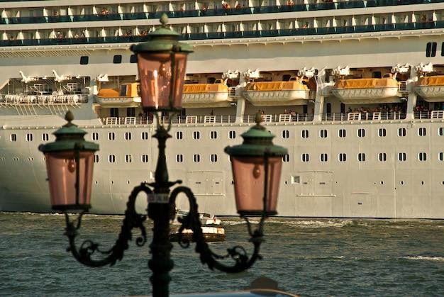 Крупным планом роскошный круизный корабль из порта на закате