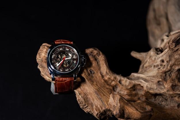 黒の背景または孤立した木材に配置された高級男性の腕時計のクローズアップ