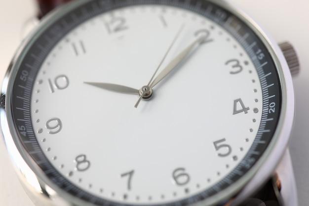 高級スイスのファッション時計のクローズアップ。ダイヤルと矢印。スタイリッシュなメンズアクセサリー腕時計。十時十。丸い形の時計の文字盤。ミニマリズムとクラシック。時間の概念