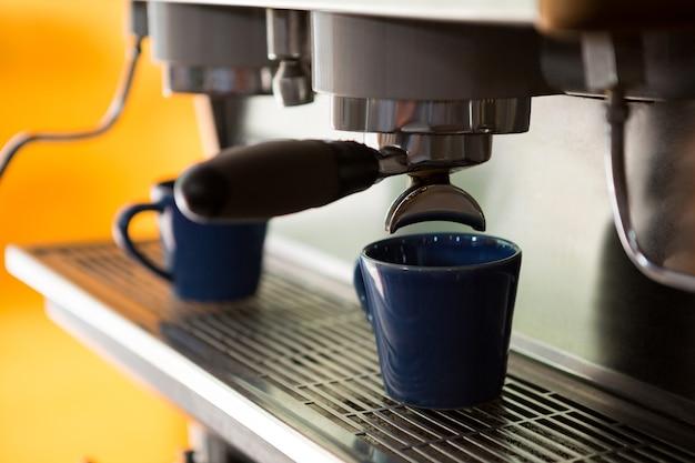 カフェで一杯のコーヒーを作る機械のクローズアップ Premium写真