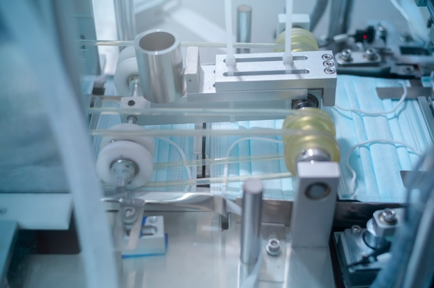 Закройте машину, производящую хирургическую маску на современном заводе, защиту от covid-19 и медицинскую концепцию.