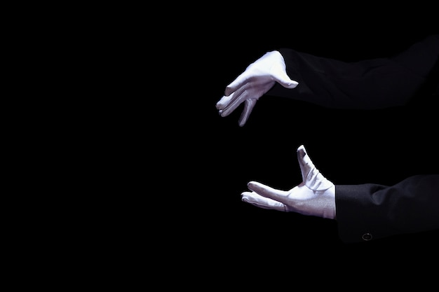 검은 배경에 흰색 장갑을 끼고 마술사의 손 클로즈업