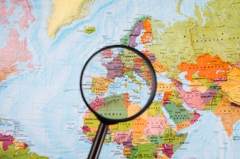Close-up of magnifying glass in front of world map