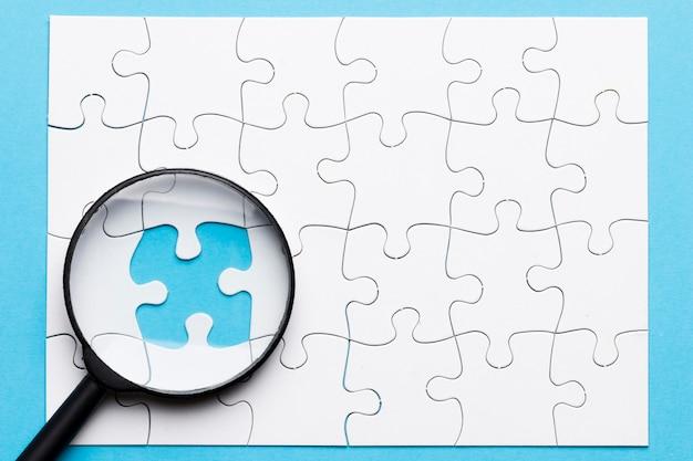 파란색 배경 위에 누락 된 퍼즐에 돋보기의 클로즈업