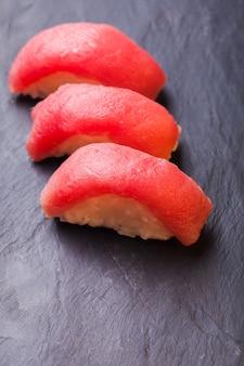 Крупный план суши магуро с тунцом на фоне черного сланца