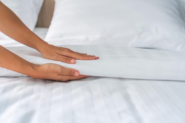 Руки горничной устанавливают белую простыню в гостиничном номере