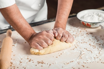 Close-up of make baker's hand kneading the dough on kitchen counter