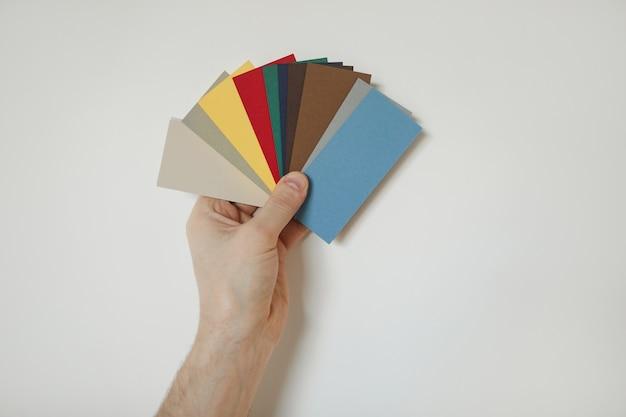 Крупным планом - рука держит образцы цветов на белой стене, выбирая дизайн для ремонта дома, копируя пространство