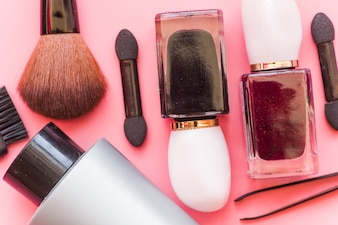 Close-up of make-up brush; cosmetics product and tweezers on pink backdrop