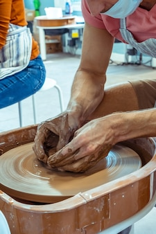 점토 도자기 만들기의 클로즈업입니다. 워크숍의 조각가가 점토를 조각합니다.