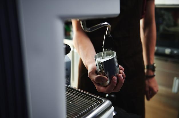 プロのスチームコーヒーマシンでミルクを泡立てて泡立てる様子のクローズアップ。飲食業界
