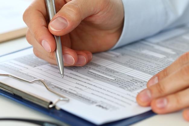 Крупным планом мужской бухгалтер, заполняющий налоговую форму. человек что-то пишет, сидя в своем офисе. заполнение индивидуальной налоговой декларации по форме 1040, составление финансового отчета, домашних финансов или концепции экономики