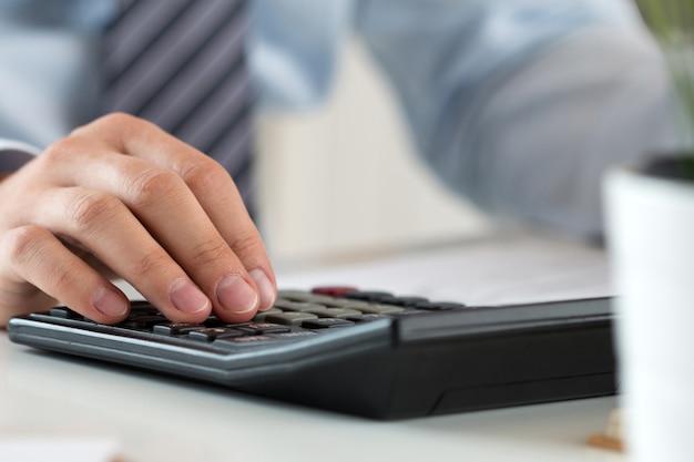 Крупным планом мужской бухгалтер или банкир расчета или проверки баланса