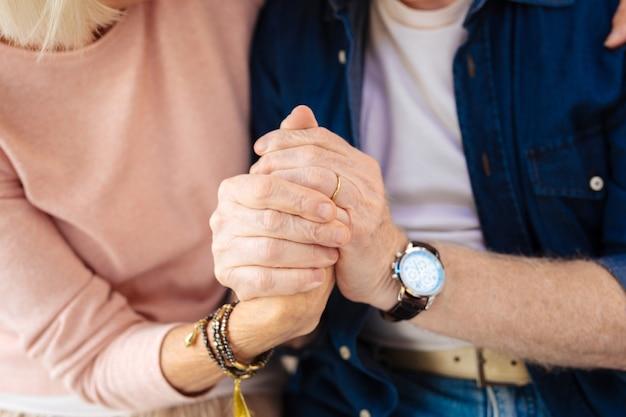 Крупным планом мужские и женские руки берут друг друга и крепко держатся