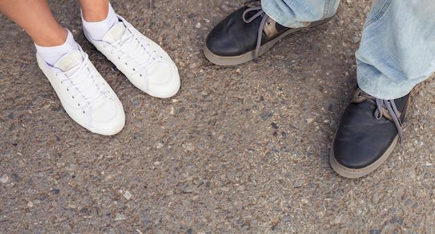 ファッションシューズの上面図の男性と女性の足のクローズアップ