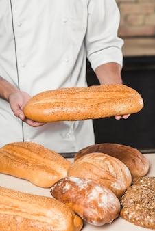 Крупный план мужской пекарь, проведение свежий хлеб