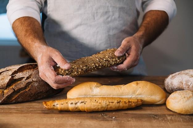 Крупный план мужского пекаря, держащего хлеб из цельного зерна на деревянном столе