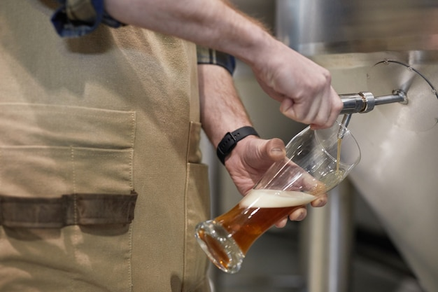 양조 공장에서 수제 맥주를 유리에 붓는 남성 양조장 클로즈업, 공간 복사