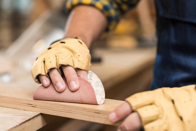 Крупным планом мужской плотник, потирая дерево наждачной бумагой