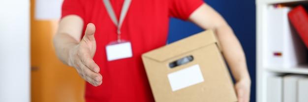 Конец-вверх мужского доставщика держа картон и трясет руку. человек в ярко-красной рубашке с именем тега. человек, дающий коробку клиенту. служба доставки и концепция интернет-магазинов