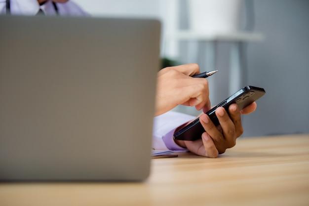 Закройте вверх мужского доктора, использующего мобильный смартфон, работающего на портативном компьютере в больнице, телеконференции или концепции телемедицины.