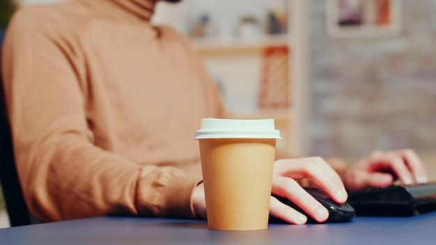 彼のホームオフィスで遅くまで働いている間に彼のコーヒーを拾う男性エンジニアのクローズアップ。