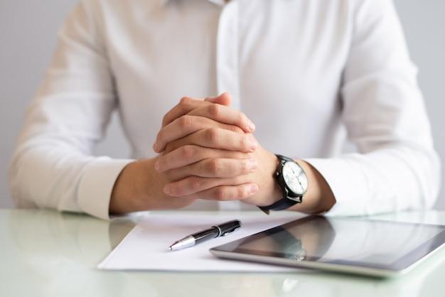Крупным планом мужской исполнительной власти, сидя за столом со сложенными руками