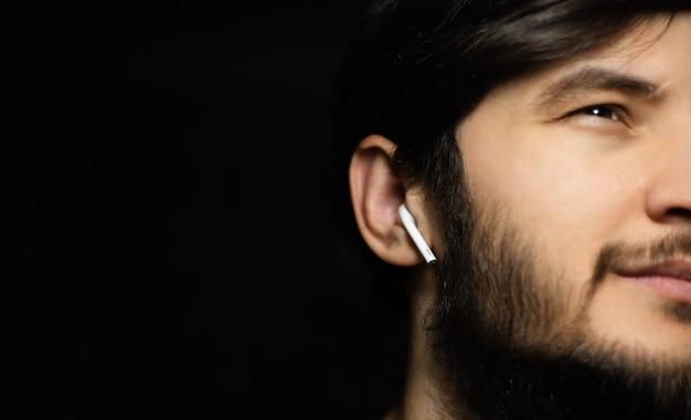 무선 이어폰을 사용 하여 검은 벽에 남성 얼굴의 클로즈업을 찾고.