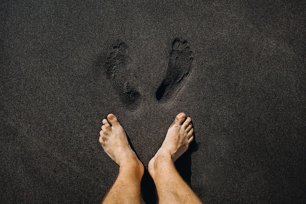 ビーチの火山の黒い砂の上を歩いている男性の足跡と足のクローズアップ。