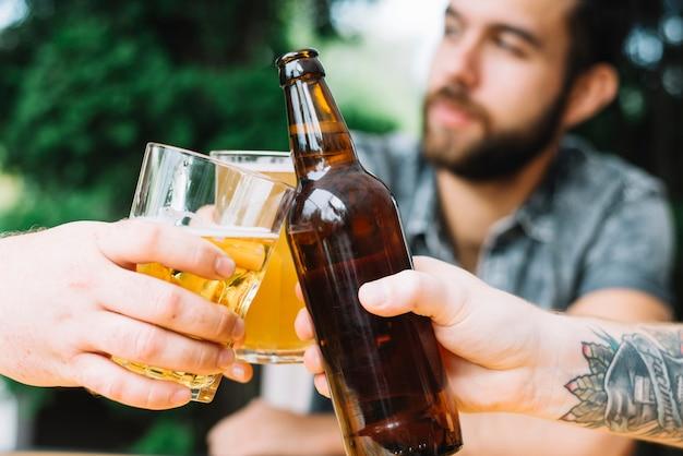 야외에서 알코올 음료와 함께 응원하는 남자 친구의 근접 촬영