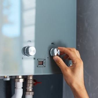 Крупный план мужской руки, регулирующей температуру водонагревателя. современный домашний газовый котел.