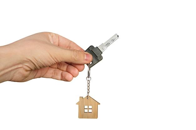 목조 주택 열쇠 고리와 열쇠를 들고 흰색 배경에서 남성 손을 닫습니다. 주택 구매 또는 임대의 개념입니다. 새 아파트의 문을 엽니다. 부동산 에이전시 광고. 키와 격리 된 손입니다.