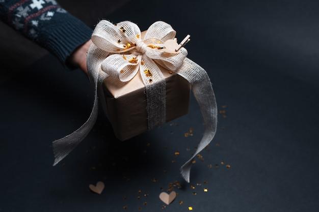 검은 색 표면에 에코 선물 상자를 들고 남성 손 클로즈업