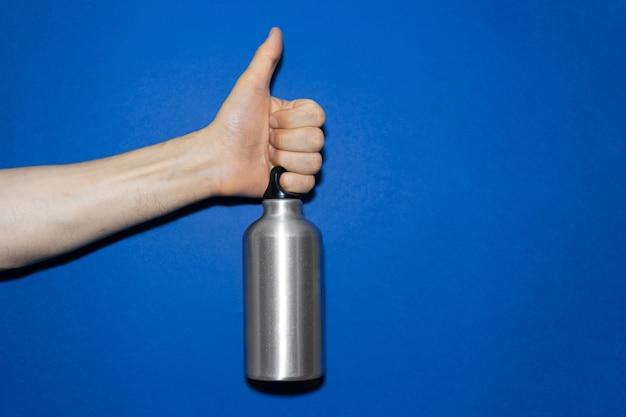 幻の青い色の背景に、親指を上に示して、アルミニウムの水筒を持っている男性の手のクローズアップ。