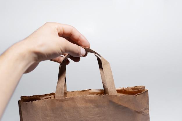 白い表面にエコ紙袋を持っている男性の手のクローズアップ