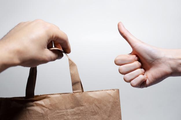 エコ紙袋を持っている男性の手のクローズアップ