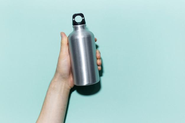 シアン、アクアメンテ色のスタジオの背景にエコ、再利用可能なアルミニウムサーモウォーターボトルを持っている男性の手のクローズアップ。