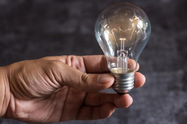電球を持っている男性の手のクローズアップ